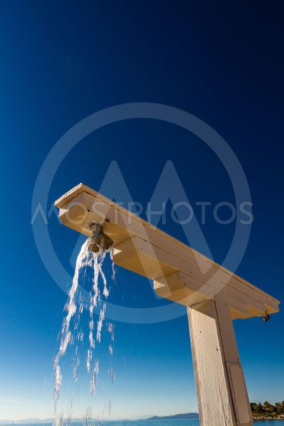 Beach shower, water flowing from it, portrait.