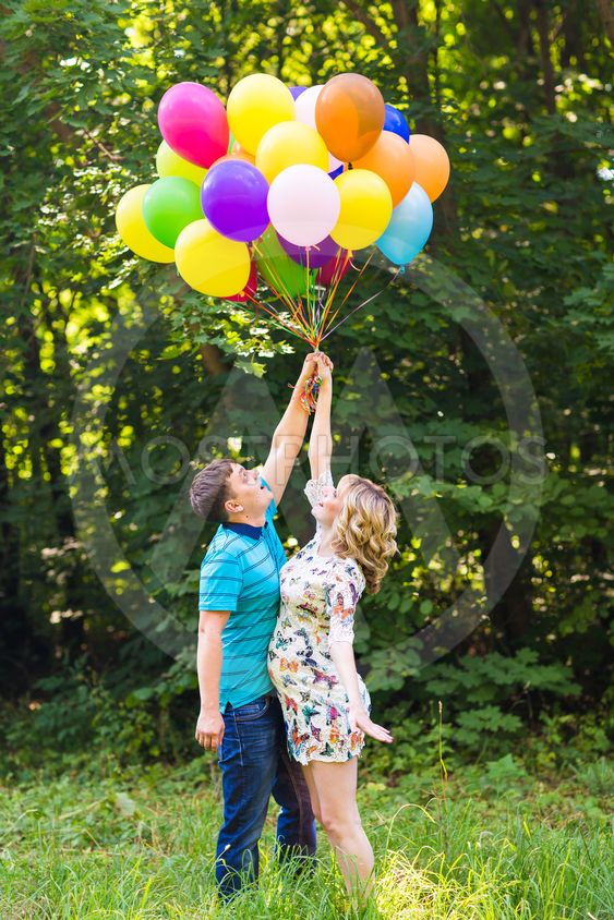 young couple man and his pregnant wife with balloons...