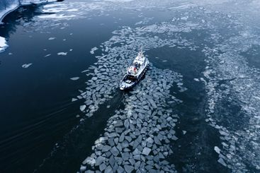 Tug boat pushing through the ice on a sea in winter