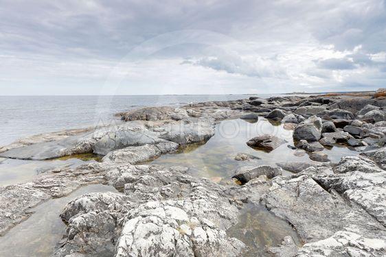 Dramatic, threatening rocky coastline, dark clouds and sea