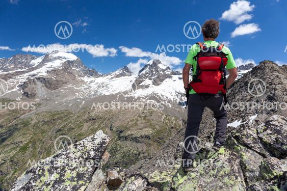 A hiker takes a rest looking at mountain panorama. Gran...