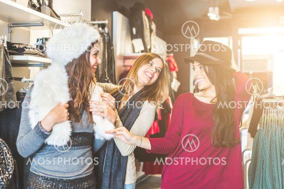 Three women in a clothing store enjoying shopping time
