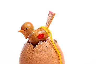 Little wooden chicken coming out of an egg