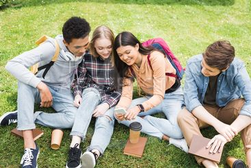 smiling and happy teenagers sitting on grass and looking...