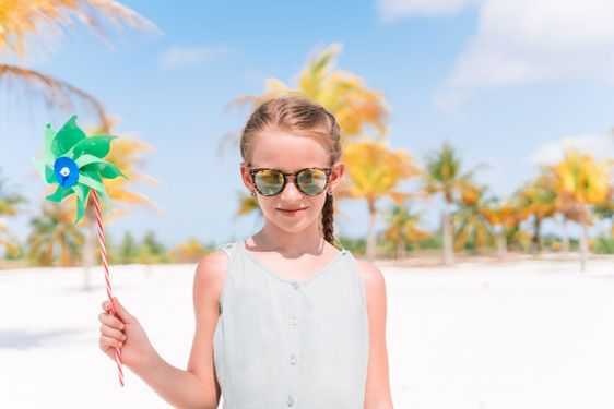 Little girl in hat walking at beach during caribbean...
