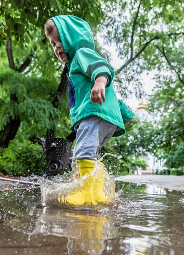 little boy is jumping in a puddle in rubber boots in...