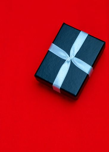 Small rectegular black gift box on a red background