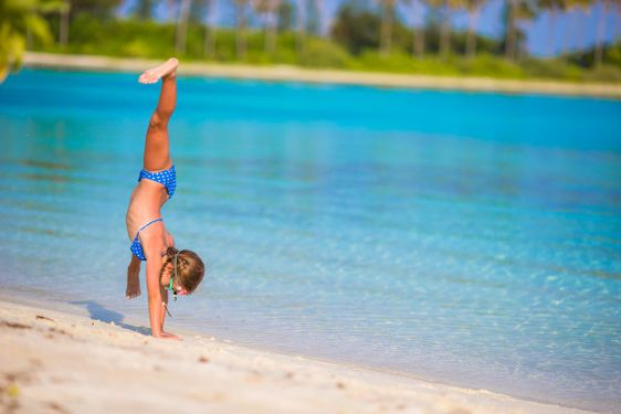 Adorable little girl having fun at beach during summer...