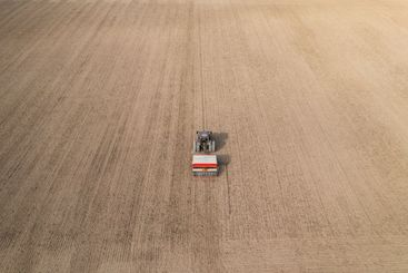 Aerial view of tractor doing farming and sowing wheat