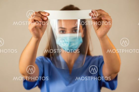 Female nurse in blue shirt holding protective face...