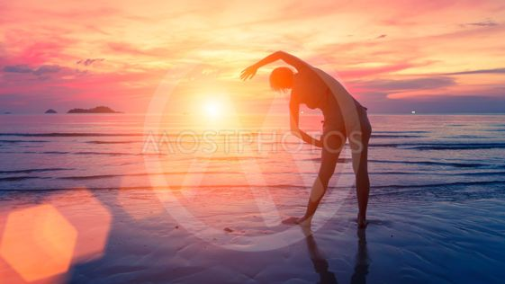 Female silhouette performs physical exercises on the...