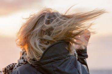 Blond kvinna med vind i håret i solnedgång - Silvertid
