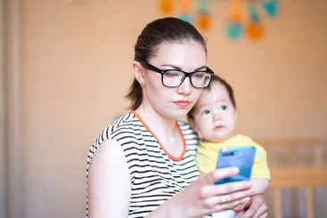 young mother with little baby on hands holds smart phone...