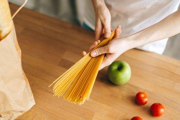 Woman hold wheat spaghetti pasta in hands. Prepare to...