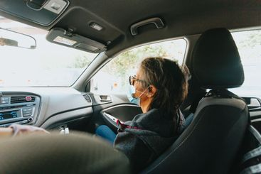 Old woman with a mask on in the front sea of a car