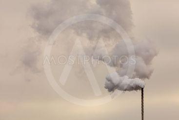 Smoke from chimney on dark cloudy sky