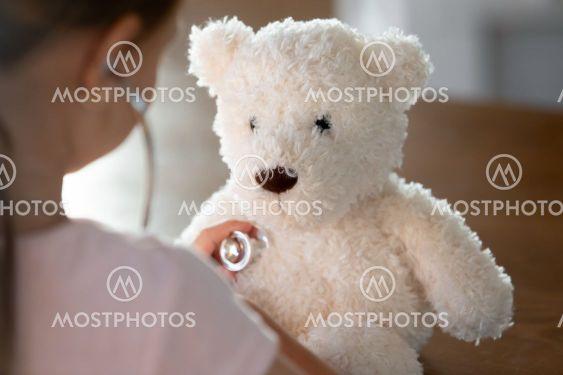 Caring little kid examine plush teddy bear