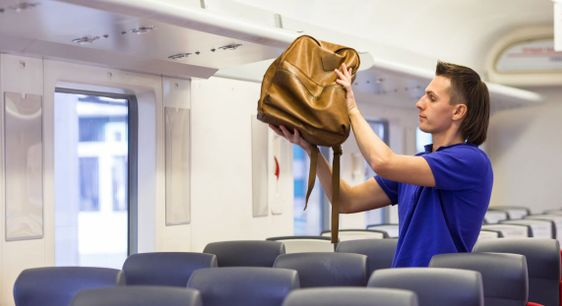 Young caucasian man putting luggage on the top shelf at...