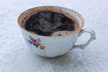 Closeup a cup of black coffee in the snow