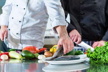 Chefs preparing food in teamwork at restaurant kitchen