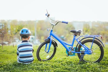Cute child in helmet and protection sits near his bike