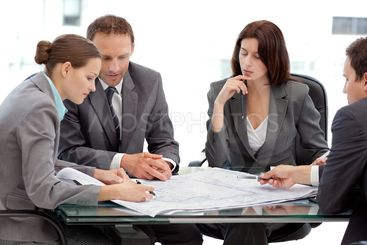 Four serious engineers looking at plans sitting at a table