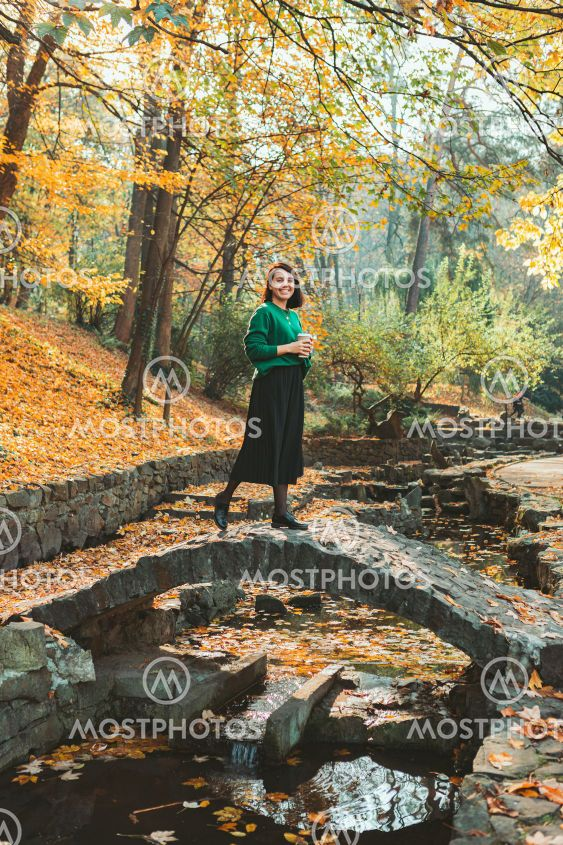 young smiling pretty woman walking by autumn city park