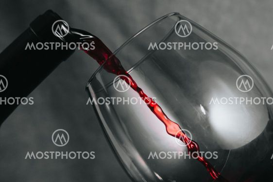 A bottle of wine serving wine in a cup with copy space...