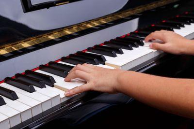 Boys hands on Piano keys.