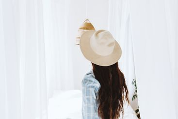 Beautiful young woman in white hat standing near bed in...