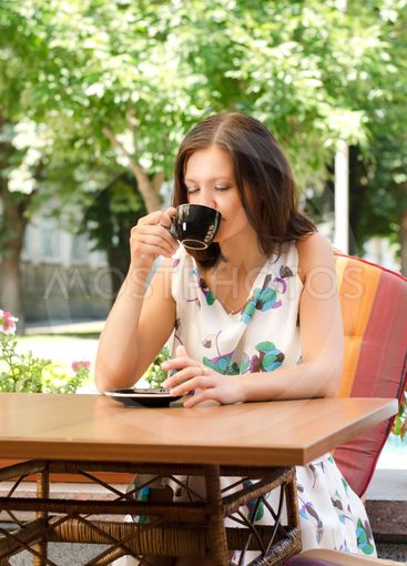 Woman drinking coffee at open-air cafe