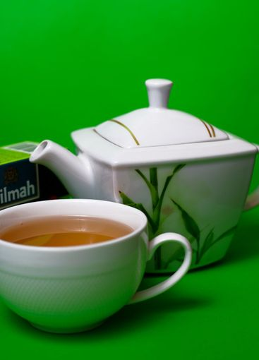 Teapot and cup of Dilmah green leaf tea