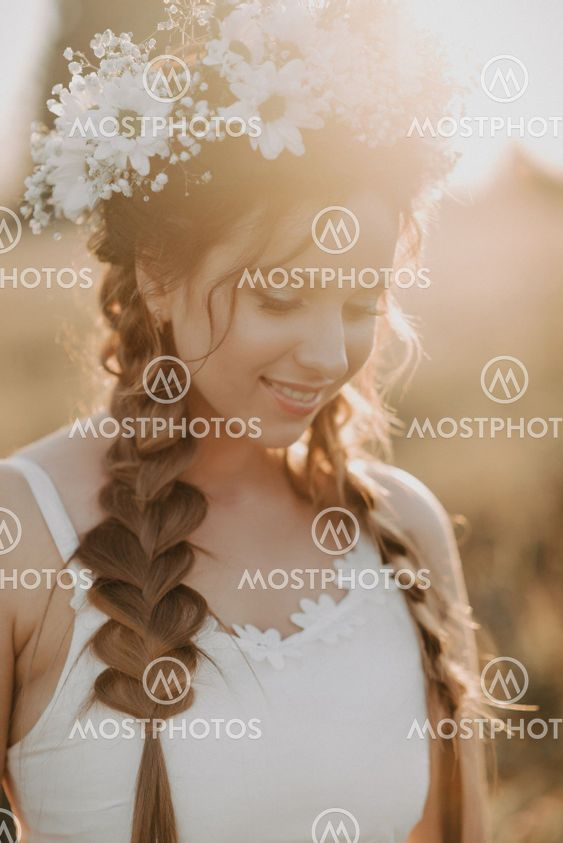 portrait of smiling girl in white dress with floral...
