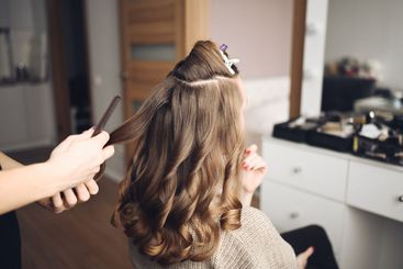 Hair stylist prepares beautiful young woman for event,...