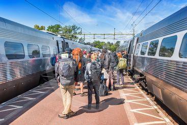 Resenärer väntar på att gå på tåg på en station