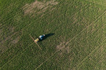 Tractor spraying chemical treatment on field
