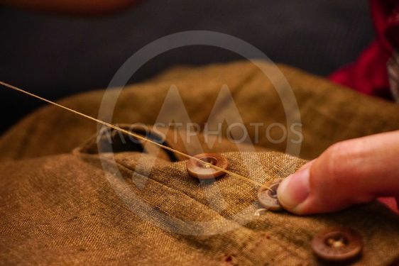 Sewing button of trousers handcraft close up view