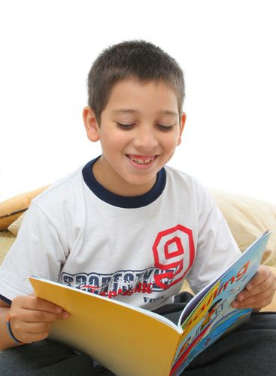 Boy reading a book on the floor