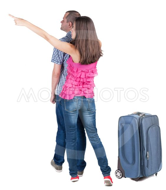 young couple traveling with suitcas and pointing at wal...
