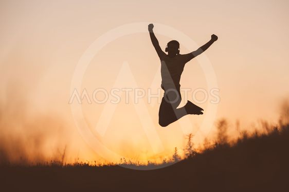 Silhouette of jumping man on sunset fiery sky background...