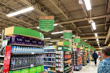 Aisles at a Publix grocery store with signs above each...