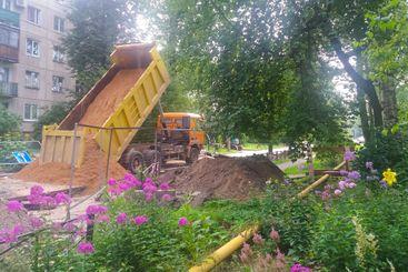 Road repair. Orange dump truck pours the sand brought