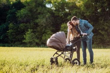 Happy family with a pram spends time outdoors