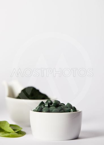 selective focus of leaves, bowls with spirulina pills and...