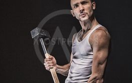 Angry muscular man with hammer