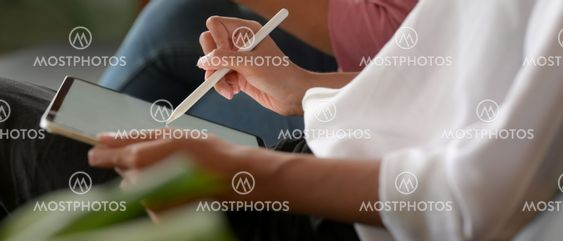 Female worker writing on mock up tablet while meeting...