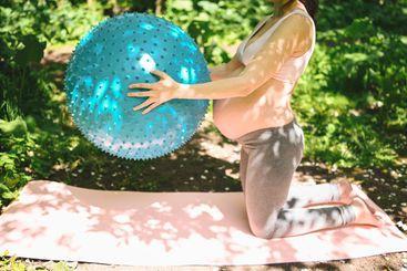Beautiful young pregnant woman doing yoga exercising...