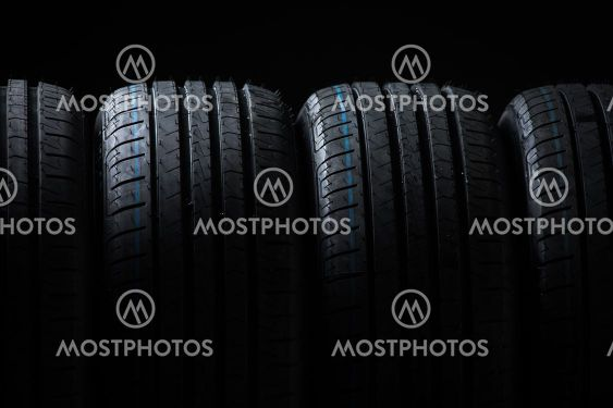 Stack of brand new high performance car tires on clean...