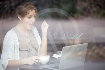 Portrait of euphoric woman looking at her laptop