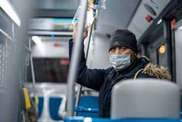 A man in a city bus wearing a protective medical mask.